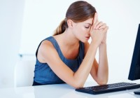 Portrait of stressed female executive with computer at office; Shutterstock ID 83085169; PO: aol; Job: production; Client: drone